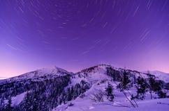 Milky Way Galaxy. Purple night sky stars above mountains Stock Image