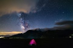 Milky way galaxy stars over the Alps, camping illuminated tent, Mars and Jupiter planet, snowcapped mountain range, astro night sk stock images