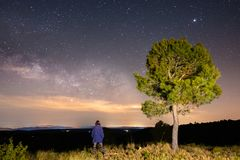 Milky Way with a girl next to the tree on the hill. Milky Way with travelers. Universe royalty free stock images