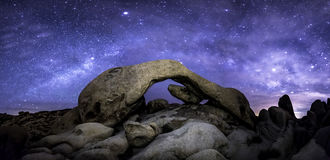 Milky Way in Joshua Tree. The Milky Way formed over Joshua Tree`s Arch Rock.  This is a panoramic perspective requiring eight stitched images to get a 180-degree Stock Photography