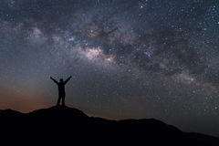 Milky Way landscape. Silhouette of Happy man standing on top of mountain with night sky and bright star on background Royalty Free Stock Photo