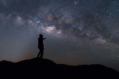 Milky Way landscape. Silhouette man thump up and standing on top of mountain with night sky and bright star on background Royalty Free Stock Photography