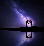 Milky Way. Man and woman holding hands in heart shape Stock Image