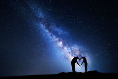 Milky Way. Man and woman holding hands in heart shape Stock Photos