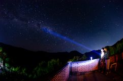 Milky Way in the mountains with a flashlight in his hands. Silhouette of man standing against the Milky Way in the mountains with a flashlight in his hands at stock image