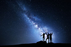 Milky Way. Night sky and silhouette of a family. Night landscape with Milky Way and people. Sky with stars and silhouette of a happy family with raised-up arms Royalty Free Stock Images