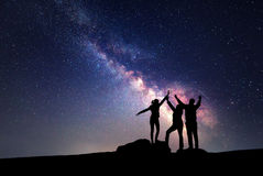 Milky Way. Night sky and silhouette of a family. Milky Way. Night sky with stars and silhouette of a happy family with raised-up arms Stock Photo