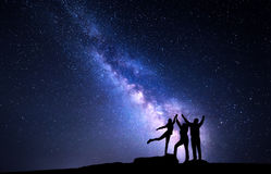 Milky Way. Night sky with silhouette of a happy family. Milky Way. Night sky with stars and silhouette of a happy family with raised-up arms Stock Images