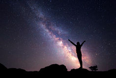 Milky Way. Night sky with stars and silhouette of a woman. With raised-up arms Stock Images