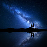 Milky Way. Night starry sky with silhouettes of a couple Stock Photos
