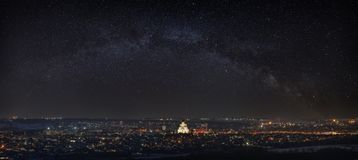 Milky Way over the city. Bright stars in the night sky. The streets are lit by lanterns. Panoramic view of the Orthodox Church. stock photo