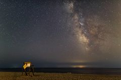 Milky Way over empty summer beach with lifeguard chair in foreground stock photo