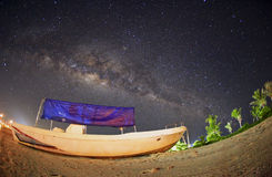 Milky way over fisherman boat at Mabul Island. Visible noise due Royalty Free Stock Image