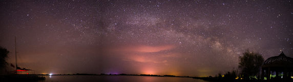 The milky way over the lake in the desert. On the right side, there is a tree and on the left side, there is a boat Royalty Free Stock Images