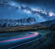 Milky Way over mountain road. Blurred car headlights stock photo