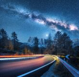 Milky Way over mountain road. Blurred car headlights stock image