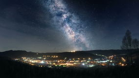 Milky Way over mountain town. Night time lapse of Milky Way over mountain town