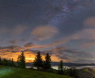 Milky way over a mountain valley with clouds Stock Images