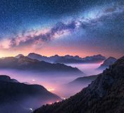 Milky Way over mountains in fog at night in summer. Landscape. With alpine mountain valley, purple low clouds, colorful starry sky with milky way, city royalty free stock photos
