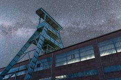 Milky way over old mine tower in germany. Milky way over old mine tower with destroyed building of zeche ewald recklinghausen germany royalty free stock images