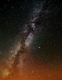 The milky way over orange lights Royalty Free Stock Image
