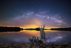 The Milky Way over a Shining Lake. Panoramic view of The Milky Way over Salt Fork lake, Ohio with interesting driftwood in the foreground Stock Photo