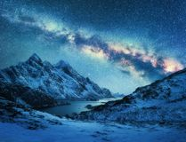 Milky Way over snow covered mountains and sea coast at night stock images
