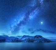 Milky Way over snow covered mountains and sea at night in winter royalty free stock images