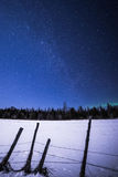 Milky way over a snow covered pasture and fenceline. At night in winter Stock Photo