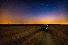 Milky way over stubble field, car and rural sandy road Royalty Free Stock Photos
