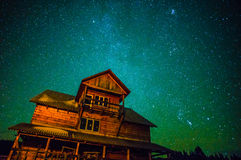 Milky way over wooden house. Night star winter sky and milky way with wooden house Stock Photography