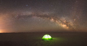 Milky Way Panorama over a lit tent. A beach camper under the milky way galaxy while the tent is illuminated Royalty Free Stock Photography