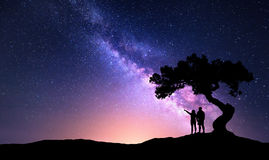 Milky Way with people under the tree on the hil Stock Image