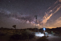 Milky Way rising behind an old windmill. Man illuminating an old windmill along a trail in Joshua Tree National park Stock Image