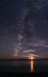 The Milky Way rising out of the sea, next to a setting Moon Stock Photo