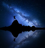 Milky Way. Silhouette of a happy man on the rock Royalty Free Stock Photography