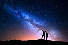 Milky Way and silhouette of happy people Royalty Free Stock Image