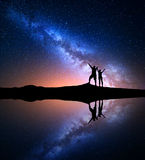 Milky Way and silhouette of happy people on the mountain Royalty Free Stock Photo