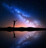 Milky Way and silhouette of a happy woman on mountain Stock Image