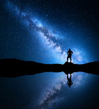 Milky Way and silhouette of a standing alone man. Milky Way. Night sky with stars and silhouette of a standing alone man on the mountain near the lake with Stock Photography