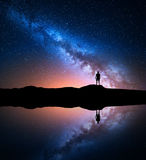 Milky Way and silhouette of a standing alone man. Milky Way. Night sky with stars and silhouette of a standing alone man on the mountain near the lake with Royalty Free Stock Photo