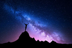 Milky Way with  silhouette of a standing happy girl. Landscape with Milky Way. Colorful night sky with stars and silhouette of a standing happy woman with raised Stock Photos