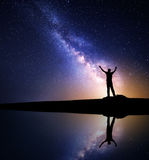 Milky Way and silhouette of a standing happy man. Milky Way. Night sky with stars and silhouette of a standing happy man with raised up arms on the mountain near Stock Images