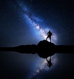 Milky Way and silhouette of a standing man near lake. Milky Way. Night starry sky and silhouette of a standing man with backpack on the stone near the lake with Royalty Free Stock Photography
