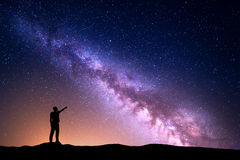 Milky Way with silhouette of a standing man pointing finger in night starry sky Stock Photos