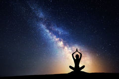 Milky Way and silhouette of a woman practicing yoga. Milky Way. Night sky with stars and silhouette of a woman practicing yoga Royalty Free Stock Photo