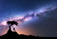 Milky Way and silhouette of woman under the tree. Growing from the rock on the mountain at night. Space background with starry sky, beautiful galaxy and girl royalty free stock photos