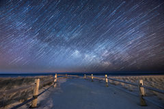 Milky Way Star Trails over a beach path. A combination of star trails and the milky way galaxy blended together for an interesting effect with a beach path as Royalty Free Stock Photography