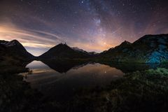 Milky Way starry sky reflected on lake at high altitude on the Alps. Fisheye scenic distortion and 180 degree view. Royalty Free Stock Photo
