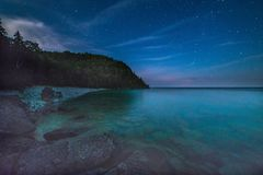 Milky way and starry sky with wispy clouds along the lakeshore o Stock Photo
